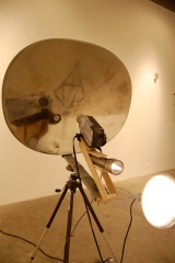 Stealth Machine, 2009, cast bronze, inflated steel, polished DirectTV dish, closed circuit television, Maglite, electric motor, steel, wood